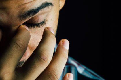 Jeune homme se frottant les yeux